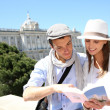 Couple reading traveler book by the Royal Palace of Madrid — Stock Photo