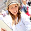Cheerful girl with hat using tablet in town — Stock Photo