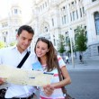 Stock Photo: Tourists reading map in front of Palacio de Comunicaciones