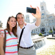 Couple taking pictures in Plaza de Cibeles, Madrid — Stock Photo