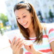 Beautiful girl using smartphone in town — Stock Photo #27931061