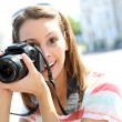 Portrait of young woman holding reflex camera — Stock Photo #27931073