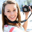 Portrait of young woman holding reflex camera — Stock Photo #27931085