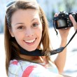 Portrait of young woman holding reflex camera — Stock Photo