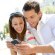 Couple of tourists in Madrid using smartphone — Stock Photo