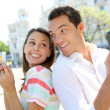 Stock Photo: Couple of tourists in Madrid using smartphone