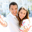 Cheerful couple with hands towards camera — Stock Photo
