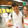 Couple in train station checking trip tickets — Stock Photo