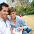 couple reading travel guide by the sagrada familia church — Stock Photo