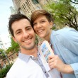 Cheerful couple with travel guide in Barcelona — Stock Photo
