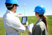 Engineers using tablet on wind turbine site — Stock Photo