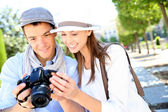Cheerful couple with photo camera in touristic area — Foto de Stock