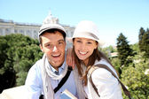 Portrait of cheerful couple in front of Palacio Real de Madrid — Stock Photo