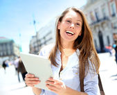 Cheerful girl with tablet walking in city — Stock Photo