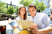 Tourists in Madrid reading city map — Stock Photo