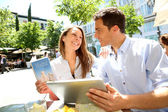 Couple connected on digital tablet in Santa Ana square — Stock Photo