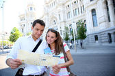 Tourists reading map in front of Palacio de Comunicaciones — Stock Photo