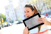 Cheerful girl in town showing tablet screen — Stock Photo