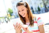 Beautiful girl using smartphone in town — Stock Photo