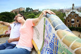 Couple of tourists relaxing on Guell Park bench — Stock Photo