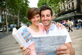 Couple looking at map in La Rambla de Barcelona — Stok fotoğraf