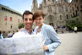 Couple looking at touristic map by Barcelona Cathedral — Stock Photo