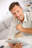 Handsome guy using tablet — Stock Photo
