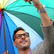 Man in town with rainbow umbrella — Stock Photo