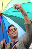 Man in town with rainbow umbrella — Stockfoto