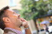 Man talking on the phone in town — Stockfoto