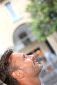 Man in town looking up — Stockfoto
