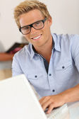 Smiling attractive young man in office — Stock Photo