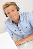Salesman with headset in conference call — Stock Photo