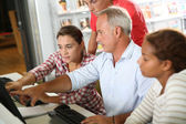Teenagers with teacher in computers' class — Stock Photo