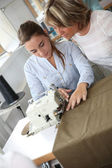 Woman in dressmaking class helping student — Stock Photo
