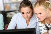 Girls in class in front of desktop — Stockfoto