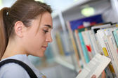Student girl reading book from school library — Stock Photo