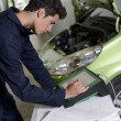 Stock Photo: Students doing car diagnostic with computer