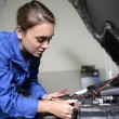 Постер, плакат: Student girl in mechanics working on car engine