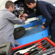 Stock Photo: Instructor showing student how to change car brakes