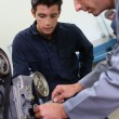 Trainer teaching student how to fix car engine — 图库照片