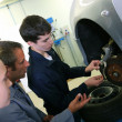 Instructor showing students how to repair car wheel — ストック写真