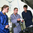 Instructor with students in repairshop changing motor oil — Stock Photo