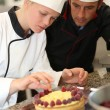 Stock Photo: Pastry cook teaching student to make cake