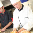Baker with students in kitchen — Stock Photo