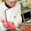 Stock Photo: Pastry cook student making red cookies
