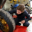 Teenager repairing motorbike — Stock Photo