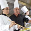 Chef teaching student how to prepare wok dish — Stock Photo #35261081