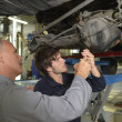 Teacher with student in car repairshop — Stock Photo