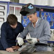 Stock Photo: Trainee with instructor using welding machine